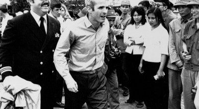 John S. McCain III is escorted by Lt. Cmdr. Jay Coupe Jr., public relations officer, March 14, 1973, to Hanoi's Gia Lam Airport after the POW was released. | AP Photo/Horst Faas