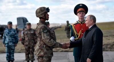 """Russian President Vladimir Putin, right, shakes hands with a Chinese serviceman as he attends military exercises on training ground """"Tsugol"""", about 250 kilometers (156 miles ) south-east of the city of Chita during the military exercises Vostok 2018 in Eastern Siberia, Russia, Thursday, Sept. 13, 2018. The weeklong Vostok (East) 2018 maneuvers launched Tuesday span vast expanses of Siberia and the Far East, the Arctic and the Pacific Oceans. They involve nearly 300,000 Russian troops along with 1,000 Russian aircraft and 36,000 tanks and other combat vehicles. (Alexei Nikolsky, Sputnik, Kremlin Pool Photo via AP)"""