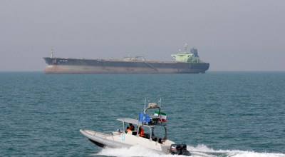 In this July 2, 2012 file photo, an Iranian Revolutionary Guard speedboat moves in the Persian Gulf while an oil tanker is seen in background. As nuclear deal threatened, Iran's politics increasingly under pressure 40 years after Islamic Revolution. In response, President Hassan Rouhan has slowly replaced his message of rapprochement with the West with hard-line hints about Iran's ability to close off the Strait of Hormuz, through which a third of all oil traded by sea passes/ (AP Photo/Vahid Salemi, File)