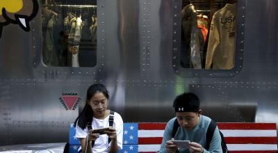Shoppers sit on a bench with a decorated with U.S. flag browsing their smartphones outside a fashion boutique selling U.S. brand clothing at the capital city's popular shopping mall in Beijing, Monday, Sept. 24, 2018. China raised tariffs Monday on thousands of U.S. goods in an escalation of its fight with President Donald Trump over technology policy and accused Washington of bullying Beijing and damaging the global economy. (AP Photo/Andy Wong)