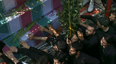 Iranian men mourn over flag-draped coffins of soldiers who were killed during the 1980-88 Iran-Iraq war and whose remains were recently recovered in the battlefields, in a massive funeral for 135 soldiers, mostly unknown, Thursday, Sept. 13, 2018. (AP Photo/Vahid Salemi).