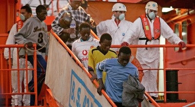 Some 38 Africans would be immigrants get off a boat helped by Spanish police officers and rescue workers after being intercepted in a fishing boat near the port of los Cristianos, in the Spanish Canary Island of Tenerife, Saturday, Aug. 26, 2006. Spain will press the European Union for more help in trying to stem the growing numbers of illegal immigrants trying to reach its shores from Africa as boats continue to arrive in unprecedented numbers. During this year more than 18,300 immigrants, mainly from sub-Sahara Africa, had landed on the Canary Islands, the highest total ever. Many die during dangerous crossing. (AP Photo/Arturo Rodriguez)