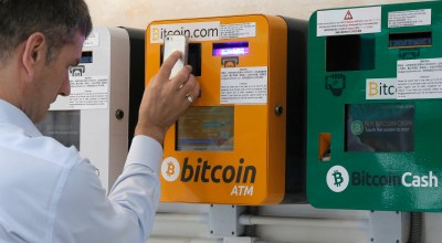 A man uses the Bitcoin ATM in Hong Kong, Friday, May 11, 2018. Bitcoin is the world's most popular virtual currency. Such currencies are not tied to a bank or government and allow users to spend money anonymously/ (AP Photo/Kin Cheung)