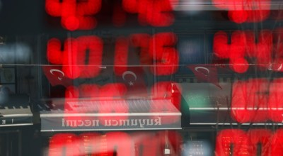 Turkish flags are reflected in the window of a currency exchange shop, displaying current rates, in Istanbul, Wednesday, Aug. 15, 2018. Many economic crises in emerging market countries like Turkey follow periods of domestic support for governments that focus on electoral gains and avoid unpopular economic reforms, and pressure on the Turkish lira is likely to persist if Turkish authorities shun decisive action, said Nafez Zouk, an analyst at Oxford Economics/ (AP Photo/Lefteris Pitarakis)