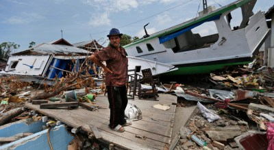 A man stands amid the damage near boats swept ashore by the tsunami in Wani village on the outskirts of Palu, Central Sulawesi, Indonesia, Thursday, Oct. 4, 2018. People living in tents and shelters have little but uncertainty since the powerful earthquake and tsunami hit the city, where death toll rises and efforts to retrieve scores more victims buried deep in mud and rubble were still hampered Thursday by the lack of heavy equipment/ (AP Photo/Dita Alangkara)
