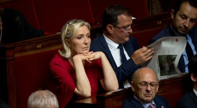 Marine le Pen, French Member of Parliament and president of the far-right 'Rassemblement National' party attends a no confidence session with her companion Louis Aliot, center right, at the National Assembly, Tuesday, July 31, 2018 in Paris. The French government faces two votes of no confidence brought by opposition parties in response to the scandal over a security aide close to French President Emmanuel Macron who is alleged to have beaten up a protester during a May Day protest. (AP Photo/Michel Euler)