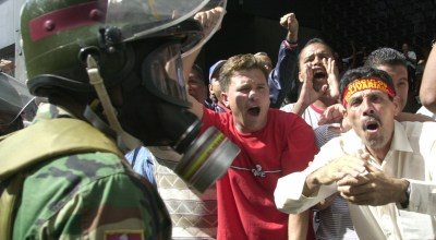 CARACUS, VENEZUELA - NOVEMBER 19: Supporters of President Hugo Chavez  yells while anti-government protesters march November 19, 2002 in Caracas, Venezuela. The opposition was protesting Chavez's takeover of the Caracas municipal police department.  Photo by Oscar Sabetta/Getty Images