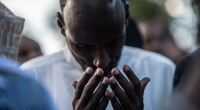 A man prays at the burial of Abdalla Mohamed Dahir and Feisal Ahmed on January 16, 2019 in Nairobi, Kenya. The two men who worked together were killed after Al-Shabab militants stormed the Dusit Hotel complex, killing 21 people. (Photo by Andrew Renneisen/Getty Images)