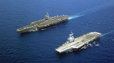 The U.S. Navy aircraft carrier USS Enterprise (CVN-65, up), the world's first nuclear-powered aircraft carrier, steams alongside the French nuclear-powered aircraft carrier Charles De Gaulle (R 91, bottom). (Wikimedia.org).