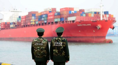 Chinese police officers watch a cargo ship at a port in Qingdao in China's eastern Shandong province on March 8, 2018. (Photo credit AFP/Getty Images)