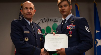 U.S. Air Force Gen. Mike Holmes, left, commander of Air Combat Command, presents a Bronze Star Medal with Valor citation to Staff Sgt. Aaron Metzger, right, 38th Rescue Squadron pararescueman, Aug. 26, 2019, at Moody Air Force Base, Ga. Metzger was awarded the medal because of his engagement in action against an enemy while deployed to Afghanistan in 2018. (U.S. Air Force photo by Airman 1st Class Taryn Butler)
