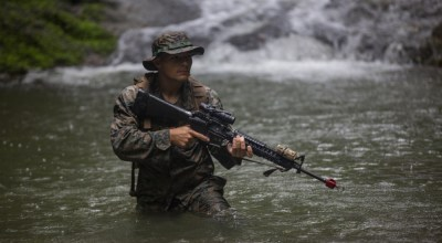 U.S. Marine Lance Cpl. Tristen Albers with Headquarters Battery, 12th Marine Regiment, 3rd Marine Division, crosses a river during the land navigation portion of the Basic Jungle Skills Course at the Jungle Warfare Training Center, Camp Gonsalves, Okinawa, Japan, August 6, 2019. The BJSC is a 5 day training event that encompasses the skills utilized in a basic jungle survival or combat environment. (U.S. Marine Corps photo by Lance Cpl. Joshua Sechser).