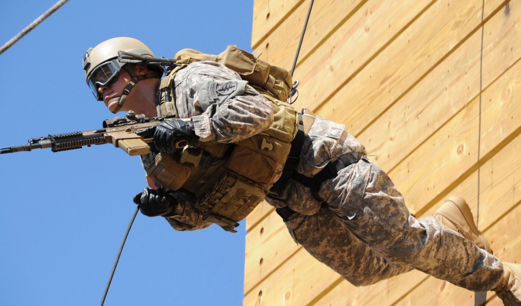 A 7th Special Forces Group (Airborne) Green Beret rappels with his weapon from a 60-foot tower at Eglin Air Force Base.