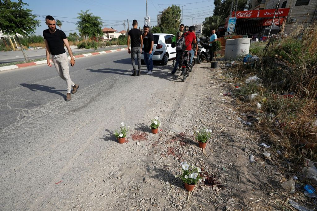 Palestinians from the West Bank town of Jenin walk by the shootout location where members of Islamic Jihad were killed and arrested by Israeli forces.