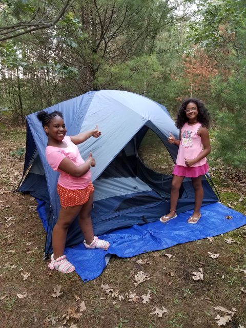 2 girls standing outside a camping tent