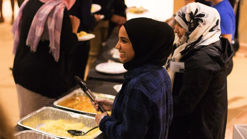 PHOTO COURTESY WHITNEY GOMES - Ramadan Tent Project volunteers Eman Al Turky and Fatima Hashmet serve the first round of food on the first night of Ramadan.