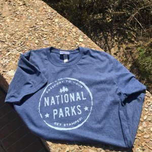 Blue shirt with white NPS Passport Stamp logo on front.