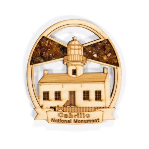 A wood magnet with the Old Point Loma Lighthouse inside the frame. Amber is used as the light rays from the lighthouse.