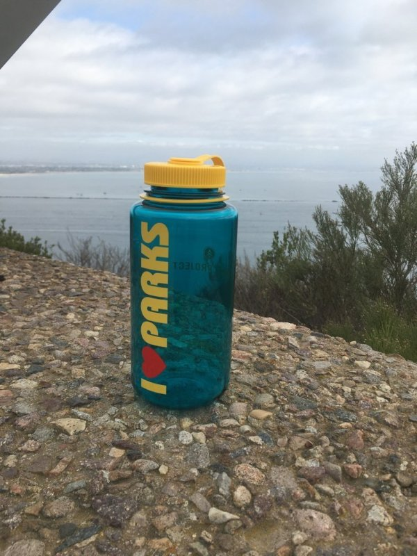 Blue translucent plastic water bottle with yellow lid. The words I Heart Parks is on the front.
