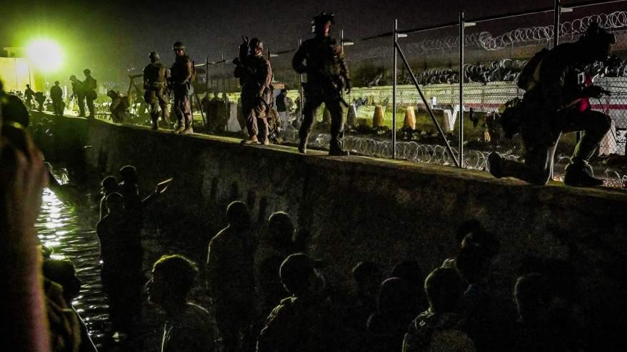 يقف جنود بريطانيون وكنديون بالقرب من قناة بينما ينتظر الأفغان خارج مطاركابول الذي تسيطر عليه قوات أجنبية، على أمل الفرار من البلاد