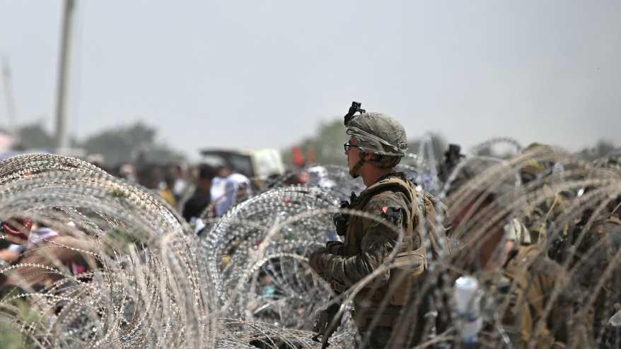 ندي أمريكي يقف في حالة تأهب بينما يتجمع الأفغان على جانب طريق بالقرب من الجزء العسكري من مطار كابول في 20 أغسطس 2021