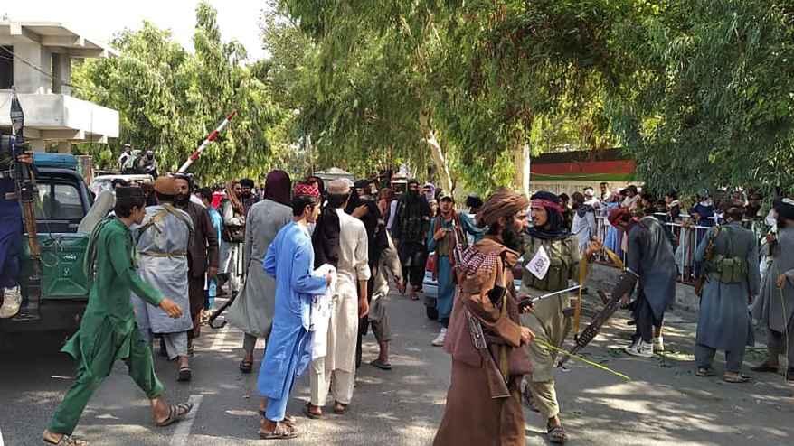 قاتلو طالبان والسكان المحليون في صورة على طول الشارع في محافظة جلال أباد، 15 أغسطس 2021