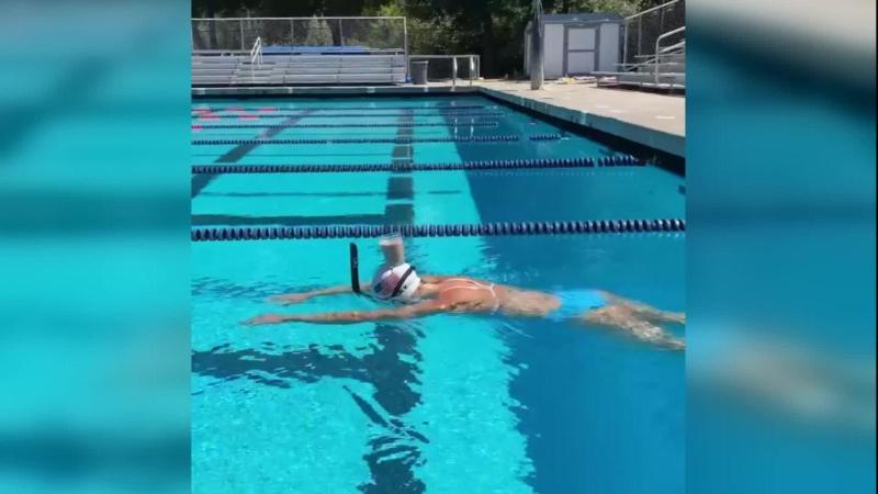Le nageur olympique traverse la piscine avec du verre sur la tête