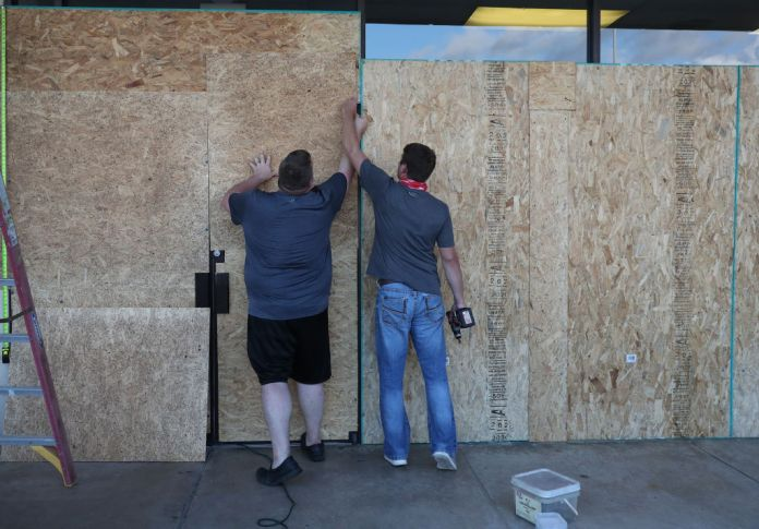 LAKE CHARLES, LOUISIANA- AUGUST 25: (L-R) Tyler Arnold and David Lohr work on placing plywood over the windows of a business before the arrival of Hurricane Laura on August 25, 2020 in Lake Charles, Louisiana. Laura is expected to hit somewhere along the Gulf Coast late Wednesday and early Thursday. (Photo by Joe Raedle/Getty Images)