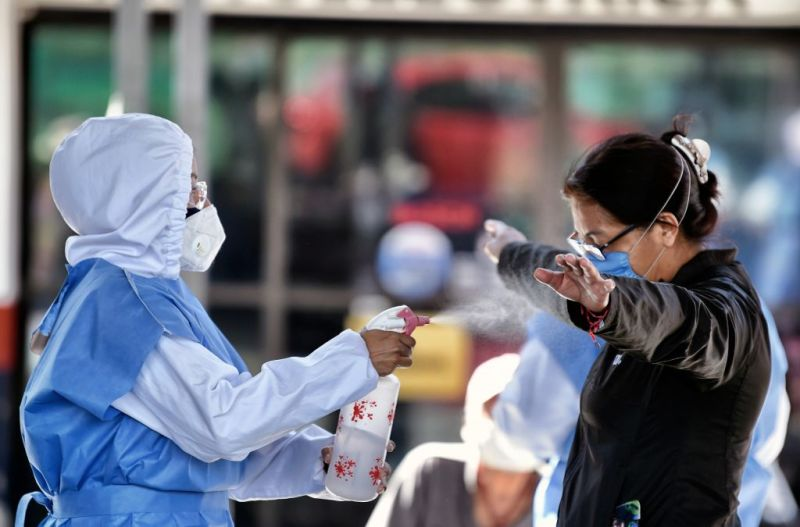 A health worker sanitizes a woman who waits for a COVID-19 rapid antigen test at a temporary health tent in Mexico City, on February 12, 2021. (Photo by ALFREDO ESTRELLA / AFP) (Photo by ALFREDO ESTRELLA/AFP via Getty Images)