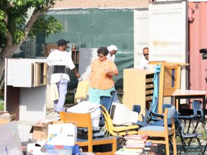 Principal Marie Martin and prisoners work side by side in the heat to unload a full container of supplies in preparation for the start of the school year