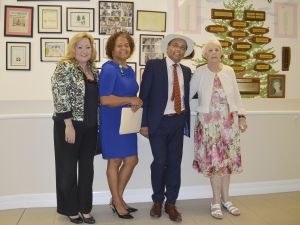 (L-R) Pines board member Pamela Webster, Pines manager Lynda Mitchell, Governor Anwar Choudhury and Pines resident Olive Miller in front of the home's Wall of History