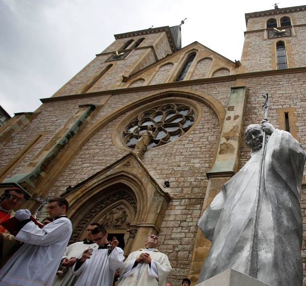 Clergymen stand outside a church during an unveiling ceremony of a statue of St. John Paul II in Sarajevo, Bosnia-Herzegovina, last year. Pope Francis announced he would visit Sarajevo June 6. (CNS/Reuters)