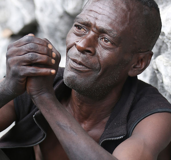 Jean-Robert Noel, who said he was homeless, sits along a street in in Port-au-Prince, Haiti, Feb. 9. Five years ago Jan. 12, a devastating earthquake rocked the poverty-stricken Caribbean nation. (CNS/Bob Roller)