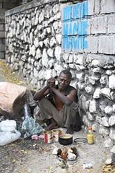 "Jean-Robert Noel cooks his meal along a street in in Port-au-Prince. The Creole sign above Robert's head says ""Let my country move forward."" (CNS/Bob Roller)"