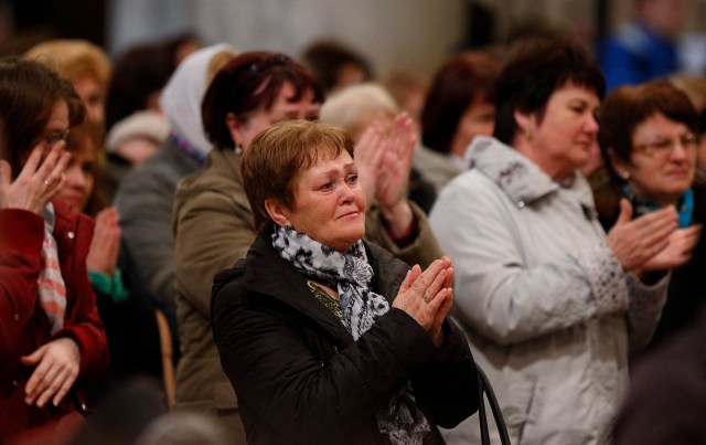 People react to a homily by Archbishop Sviatoslav Shevchuk of Kiev-Halych, leader of the Ukrainian Catholic Church, during a Divine Liturgy for Ukrainian expatriates at the Basilica of St. Mary Major in Rome Feb. 19. (CNS/Paul Haring)