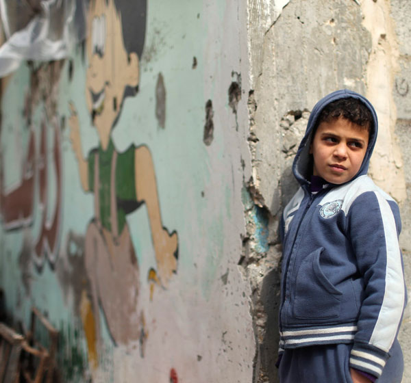 A Palestinian boy stands by a Gaza school that witnesses said was badly damaged by Israeli shelling during a 50-day war last summer. (CNS/Reuters)