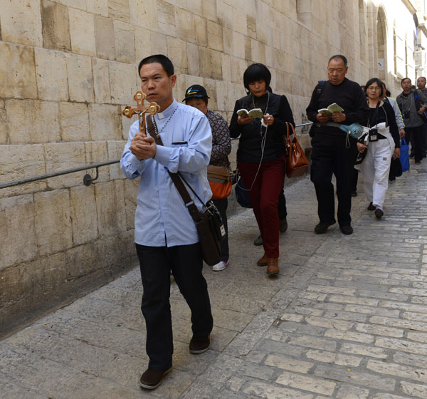 Christians from China carry a cross on the Via Dolorosa in the Old City of Jerusalem earlier this month. (CNS/Debbie Hill)