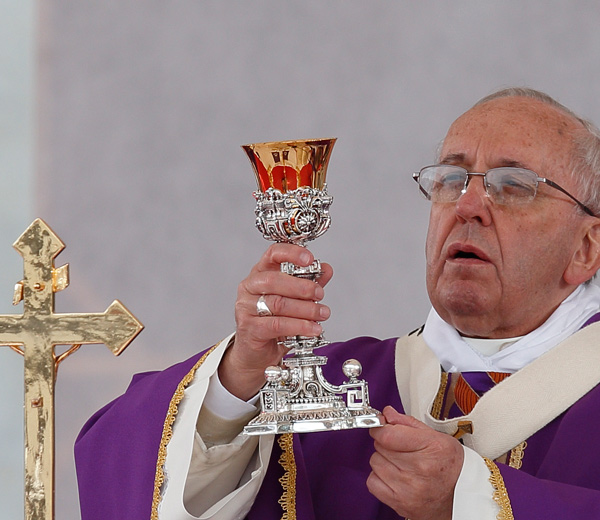 Pope Francis elevates the Eucharist while celebrating Mass in Piazza Plebiscito in Naples, Italy, March 21. (CNS photo/Paul Haring)