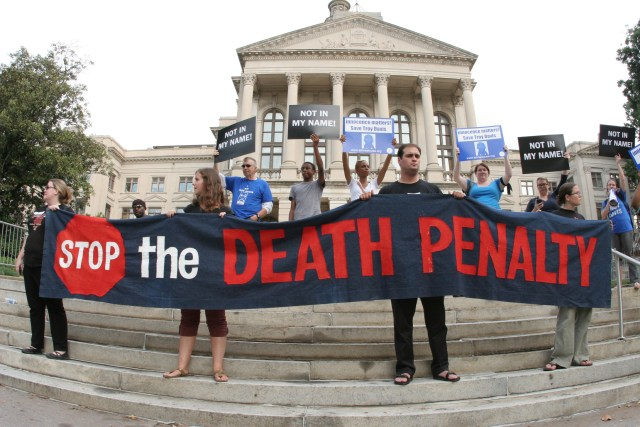 People hold a banner and signs on the steps of the Georgia Capitol in Atlanta during a 2011 vigil for a Georgia death-row inmate before his execution. (CNS file/Michael Alexander, Georgia Bulletin)