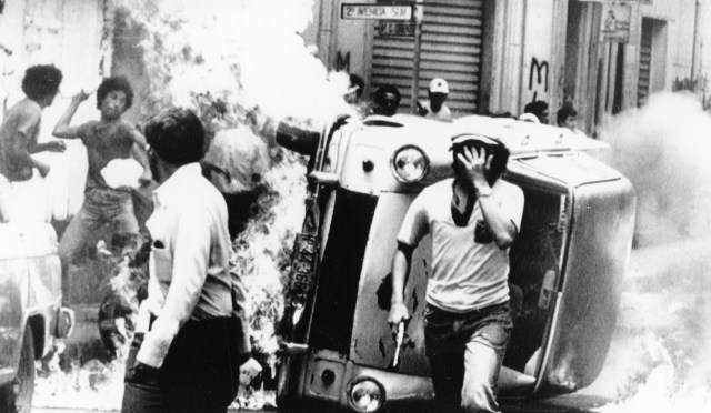 A man armed with a pistol runs from a burning car as another throws a Molotov cocktail during violence that erupted at Archbishop Oscar Romero's funeral in San Salvador, El Salvador. Several dozen people were killed after panic set in following a bomb explosion and gun shots during the outdoor funeral March 30, 1980. (Scan of CNS file photo)