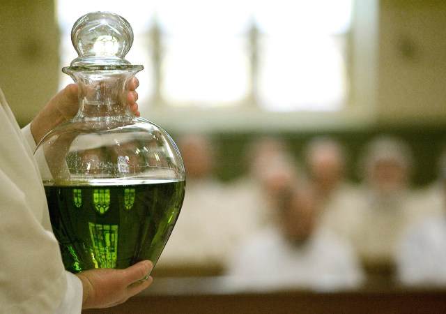 During a Chrism Mass a stained-glass window is reflected through a vessel containing oil to be used to anoint the infirm. (CNS file/Dave Crenshaw, Eastern Oklahoma Catholic)