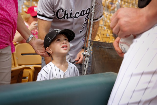 A young fan looks up to Tyler Flowers of the Chicago White Sox as the catcher signs baseballs during spring training at Camelback Ranch ballpark in Glendale, Arizona. (CNS/Nancy Wiechec)