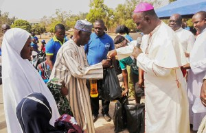 Archbishop Ignatius Kaigama presents relief material to internally displaced persons in Jos, Nigeria. Many now flee to neighboring Cameroon to escape Boko Haram attacks. (CNS/EPA)