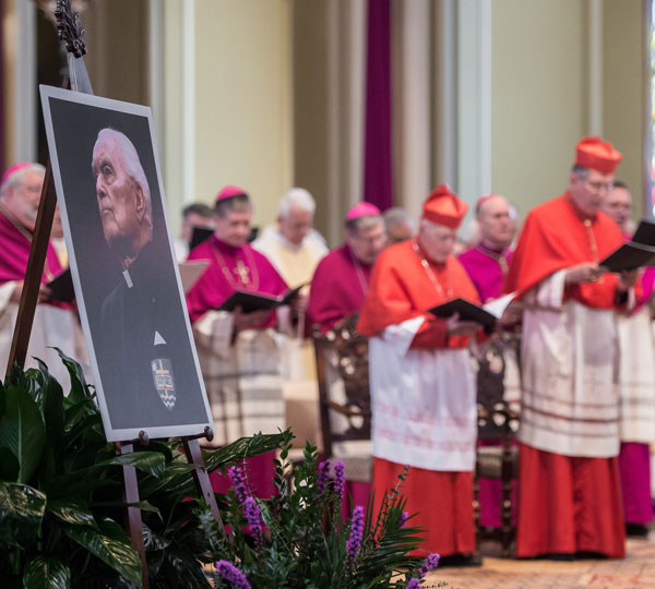 Prelates pray near a large portrait of Holy Cross Father Theodore Hesburgh, former president of the University of Notre Dame, during his funeral Mass March 4 at the Basilica of the Sacred Heart on the university's campus. Father Hesburgh died Feb. 26 at age 97. (CNS/University of Notre Dame)