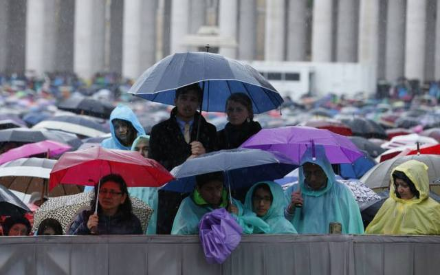 People huddle under umbrellas as they wait for the start of Pope Francis' celebration of Easter Mass in St. Peter's Square. (CNS/Paul Haring)