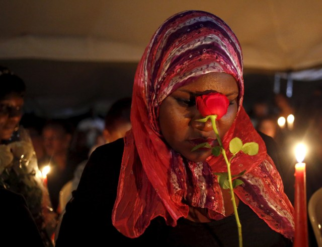 A woman prays during a memorial vigil in Nairobi, Kenya, April 7, for the 147 people killed in an attack on Garissa University College. Kenyan bishops are urging the government to step up security and for citizens to remain united after al-Shabab militants attacked the college campus April 2. (CNS/Reuters)