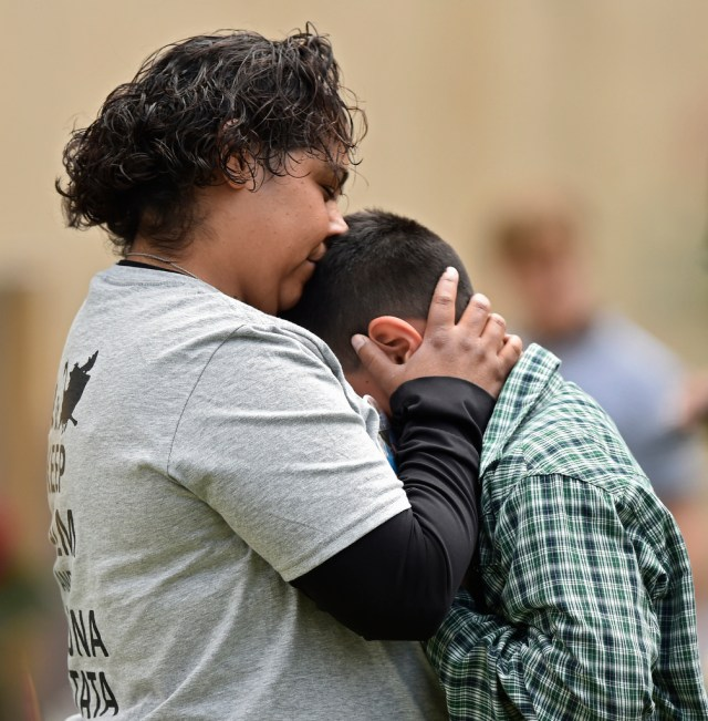A woman comforts a boy April 19 in Oklahoma City during the remembrance ceremony on the 20th anniversary of the Oklahoma City bombing at the Oklahoma City National Memorial & Museum. (CNS/Larry W. Smith, EPA)