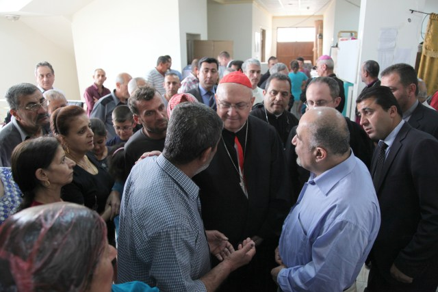 Cardinal Leonardo Sandri, prefect of the Congregation for Eastern Churches, speaks with displaced Iraqis May 4 in Irbil, Iraq. (CNS/John E. Kozar, CNEWA)