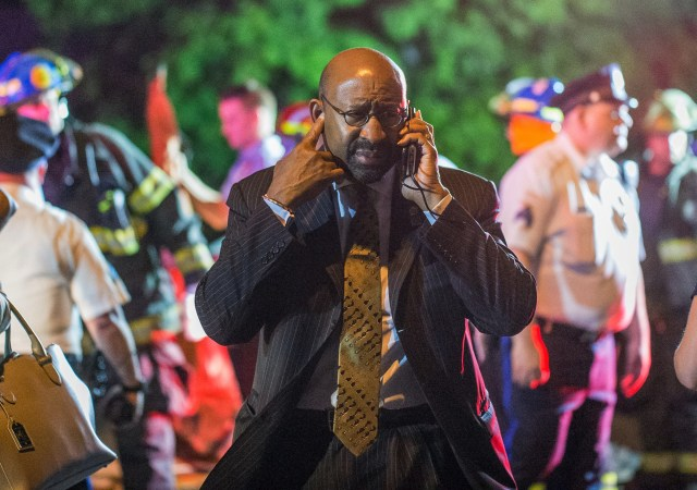 Philadelphia Mayor Michael Nutter speaks on a cellphone as emergency responders search for passengers following an Amtrak train derailment in Philadelphia May 12. (CNS/Reuters)