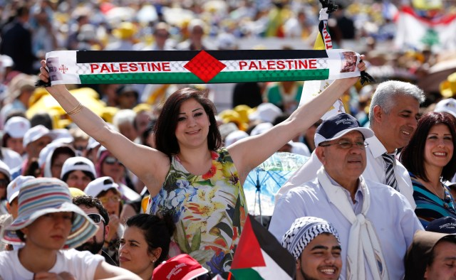 A woman holds a banner with the colors of the Palestinian flag before the start of the canonization Mass for four new saints celebrated by Pope Francis in St. Peter's Square at the Vatican May 17. Two of the four 19th-century nuns canonized by the pope were from historic Palestine. (CNS/Paul Haring)